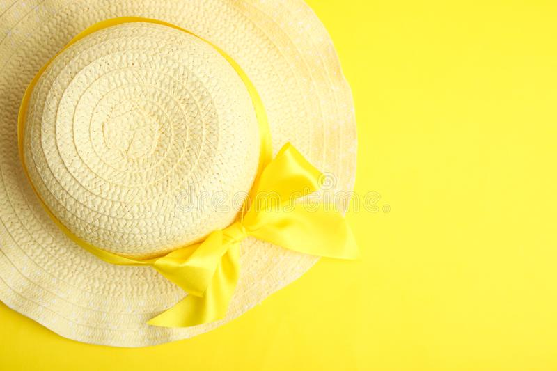 Summer beach hat. Female summer beach hat with a bow on a yellow background. Top view, copy space royalty free stock images