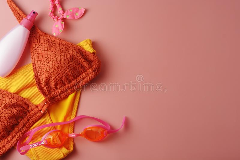 Female summer bikini swimsuit and accessories over pink background with copy space stock photo