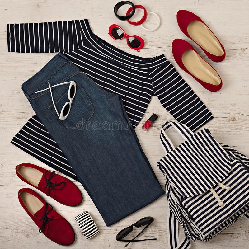 Female summer outfit - navy jeans, striped top, sunglasses, back stock image