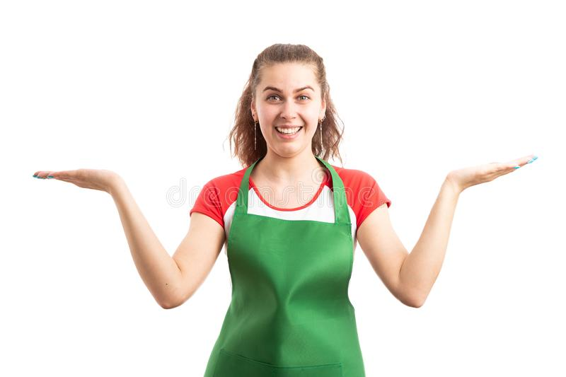 Female supermarket or retail employee presenting alternatives. Young female supermarket or retail employee presenting alternatives with copy space as choice stock images