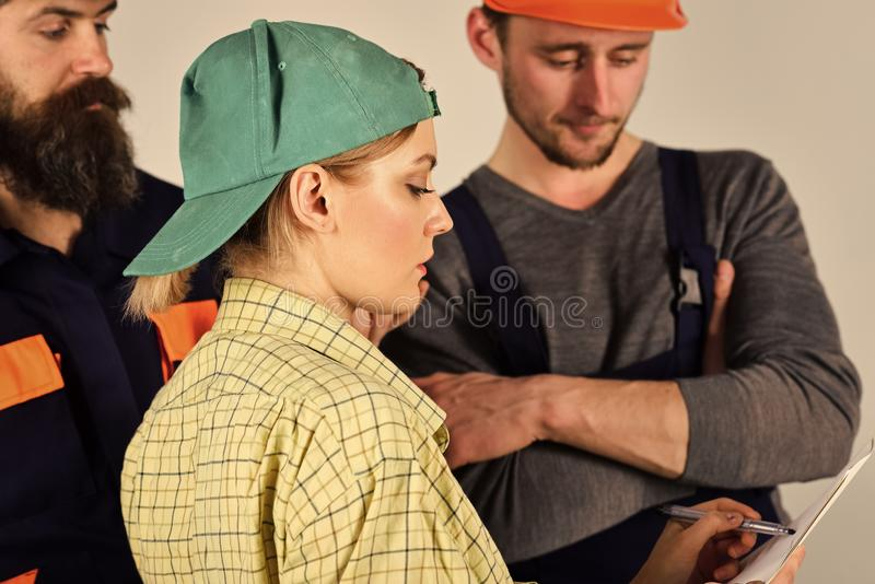 Female supervisor concept. Misunderstanding between client and worker. Young Housewife Woman Arguing With Male Plumbers stock photo