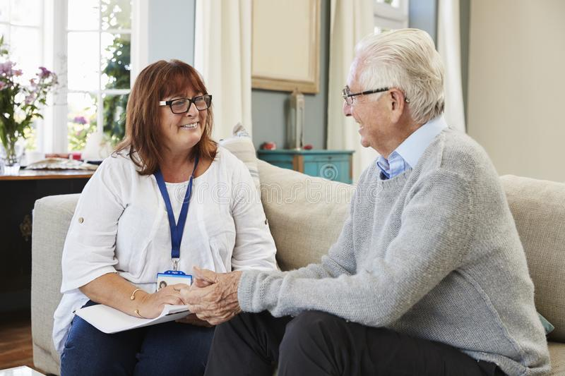 Female Support Worker Visits Senior Man At Home stock image