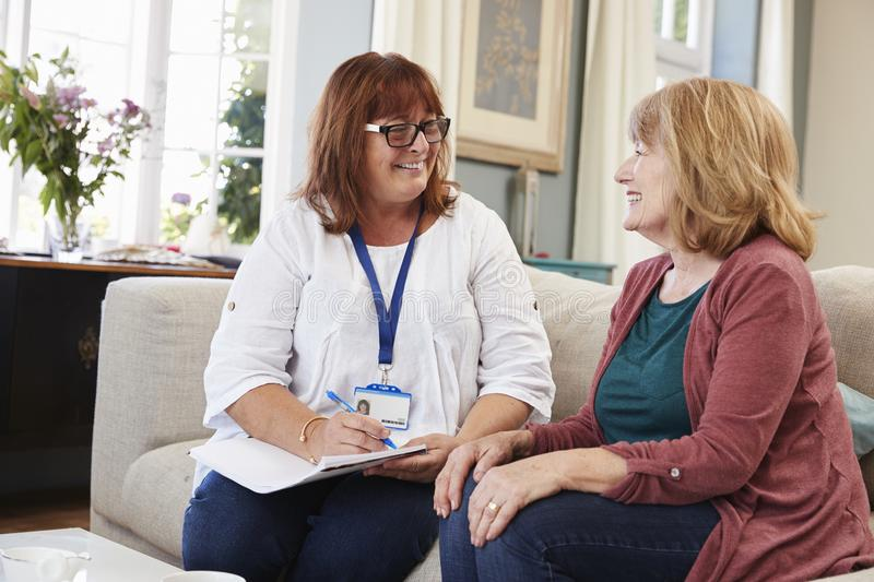Female Support Worker Visits Senior Woman At Home stock image
