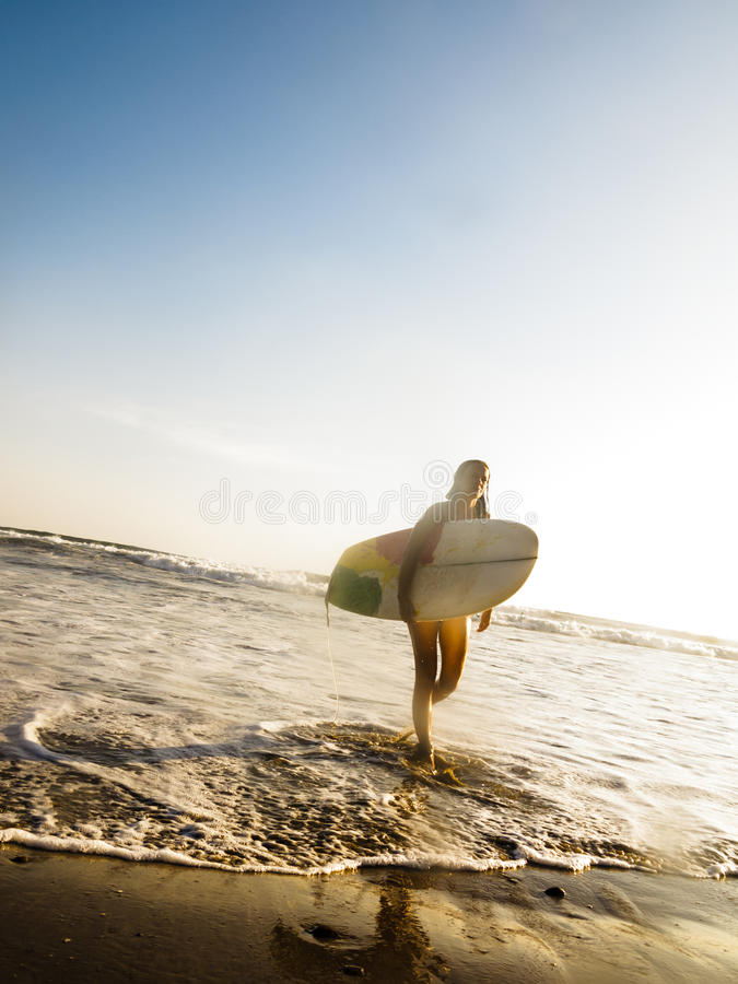 Female surfer with surf board walking on beach stock images