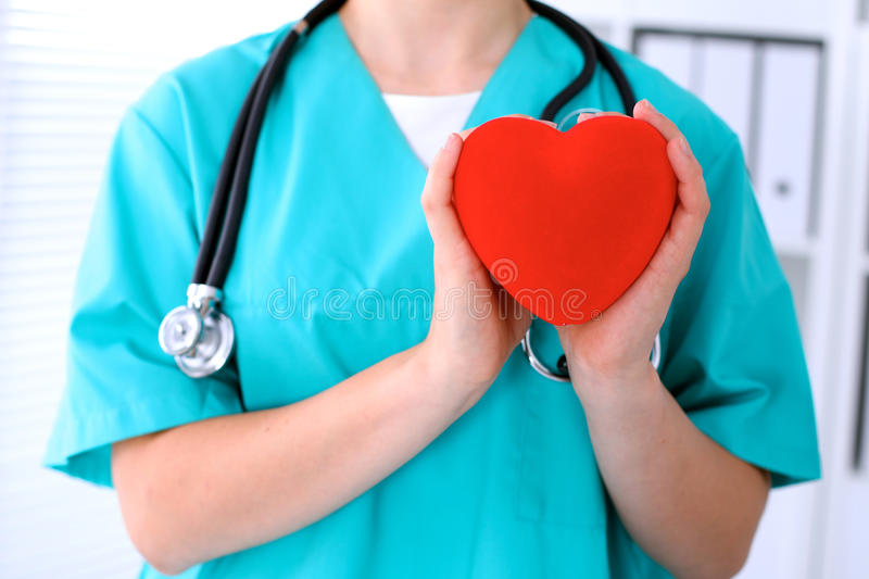 Female surgeon doctor with stethoscope holding heart.  royalty free stock photography