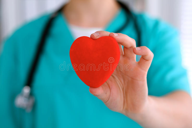 Female surgeon doctor with stethoscope holding heart.  stock photo