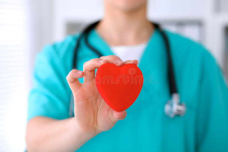 Female surgeon doctor with stethoscope holding heart. Female surgeon doctor with stethoscope holding heart royalty free stock images