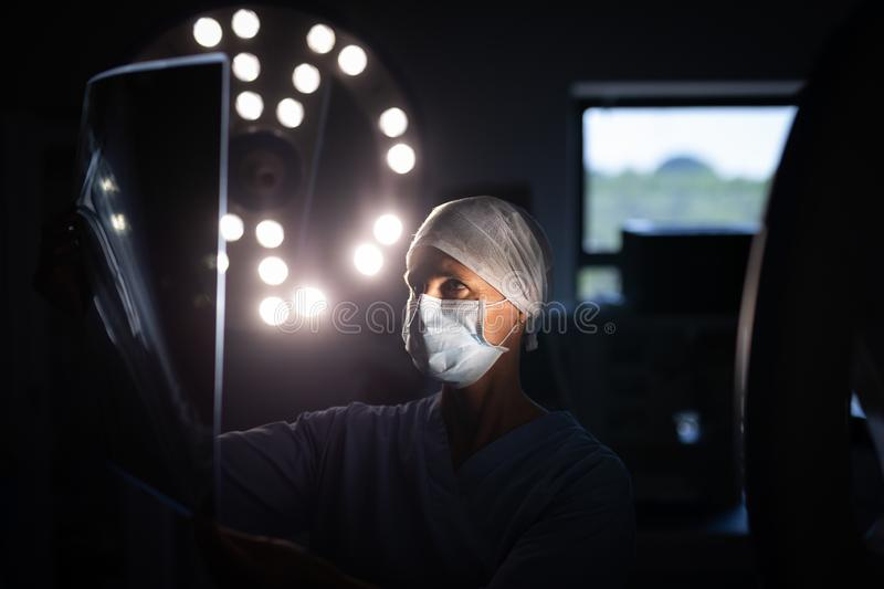 Female surgeon looking at x-ray picture in operation room royalty free stock photo