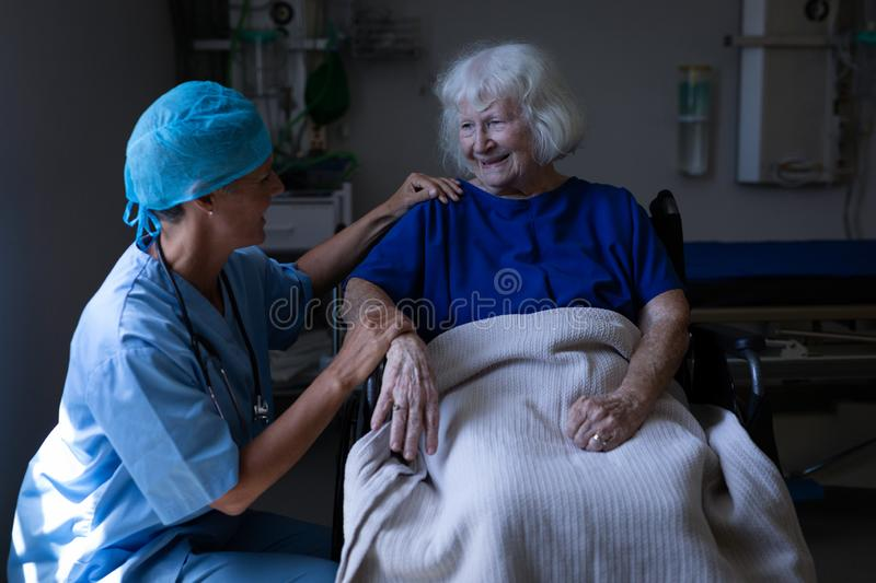 Female surgeon and senior patient talking with each other in clinic royalty free stock photo
