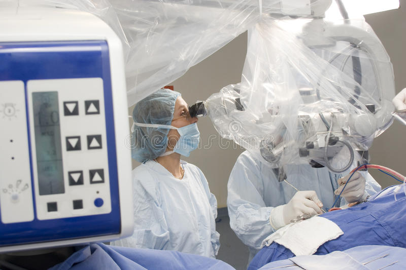 Female Surgeon Using Operating Microscope. In Hospital royalty free stock images