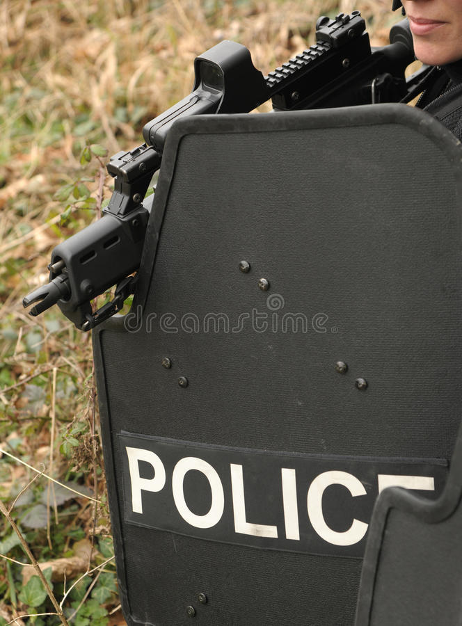 Female SWAT with ballistic shield. ENGLAND. MARCH 2012. A female police firearms officer armed with a Heckler and Koch G36C assault rifle takes cover behind a royalty free stock photography