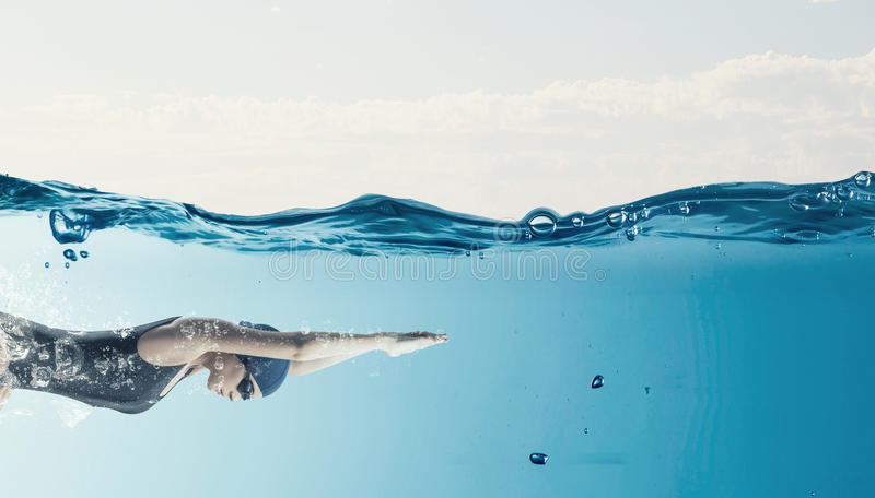 Female swimmer. Concept image. Young woman swimmer in cap and glasses under water royalty free stock photo