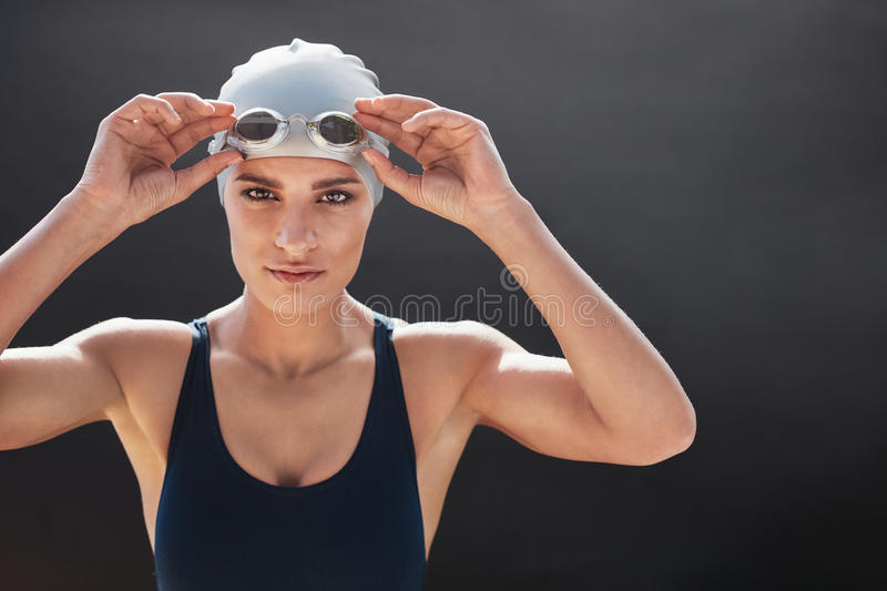 Female swimmer posing on black background. Shot of a young female swimmer isolated on black background. Fit young woman in swimming costume with copy space royalty free stock photos