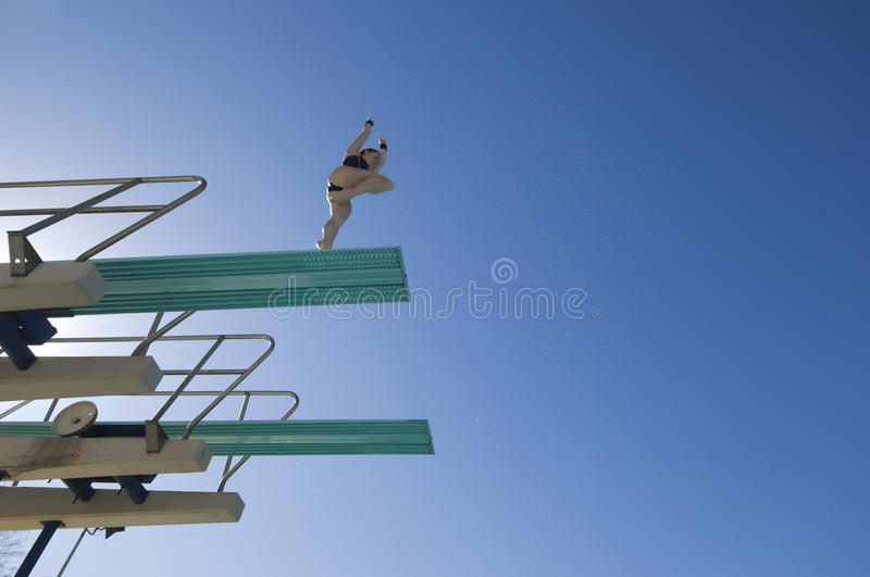 Female Swimmer Preparing To Dive Off Diving Board stock photo