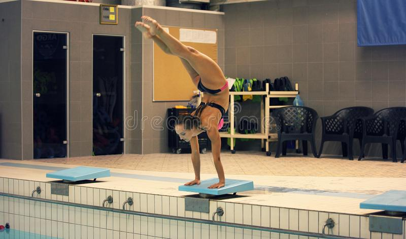 A female swimmer, that ready to jump into indoor sport swimming pool. standing on arms with legs up stock image