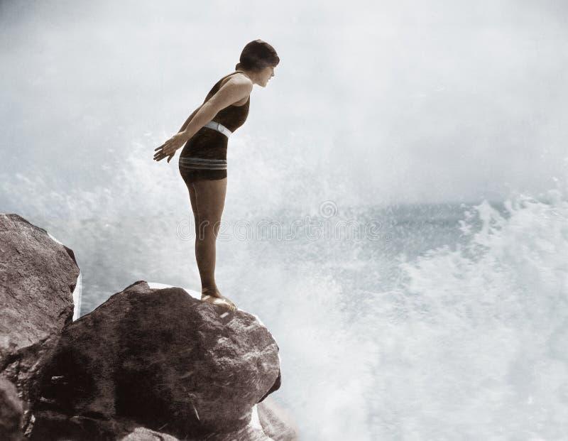 Female swimmer on rock above crashing surf royalty free stock photo