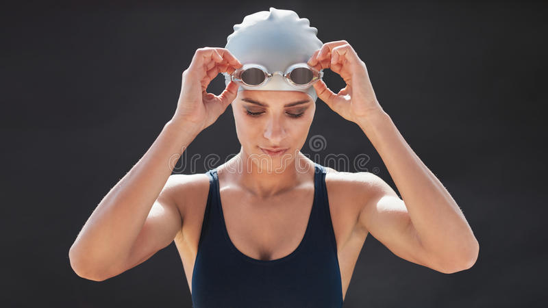 Female swimmer in a swimsuit adjusting her goggles. And looking down isolated on black background. Fit young woman in swimming costume stock photos