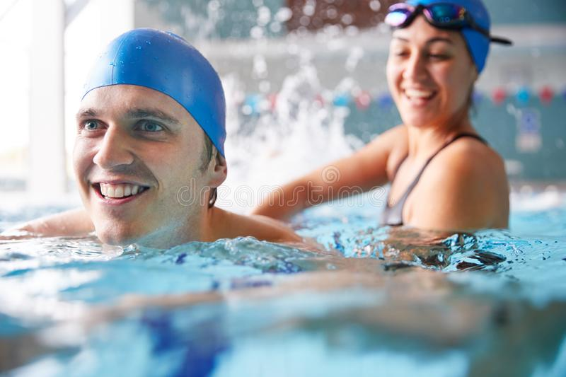 Female Swimming Teacher Giving Man One To One Lesson In Pool royalty free stock photo