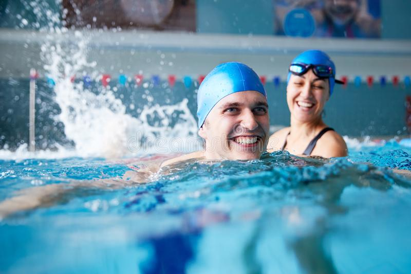 Female Swimming Teacher Giving Man One To One Lesson In Pool stock photo