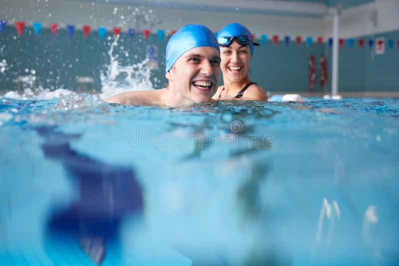 Female Swimming Teacher Giving Man One To One Lesson In Pool royalty free stock photos