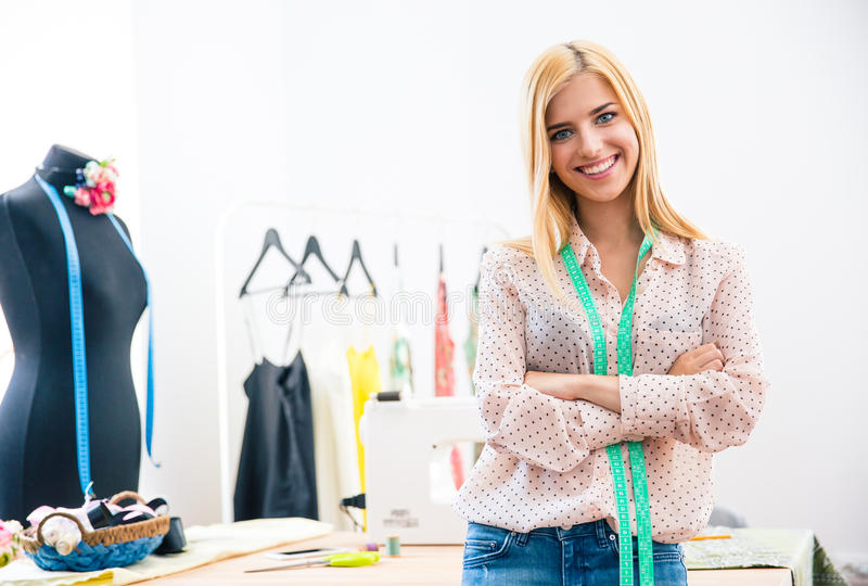 Female tailor with arms folded. Happy female tailor with arms folded standing in workshop royalty free stock photos