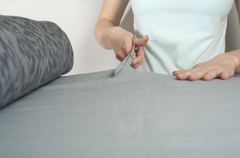 Female tailor cuts with scissors bolt of dark blue cloth. Closeup. royalty free stock photos