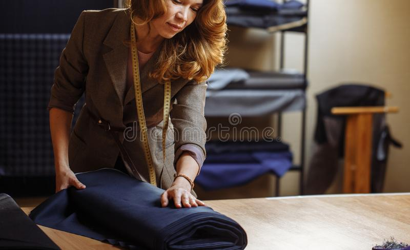 Female tailor choosing fabric for pattern cutting. Men`s Wear industry, tailoring process Concept. Female tailor examines a roll of fabric for pattern cutting at stock photo