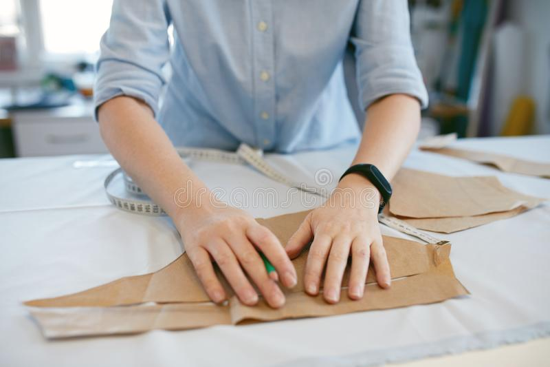 Female Tailor Making Sewing Patterns On Table stock photo