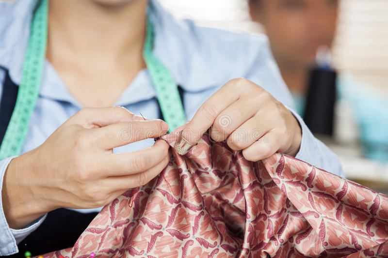 Female Tailor Stitching Textile In Sewing Factory royalty free stock photography