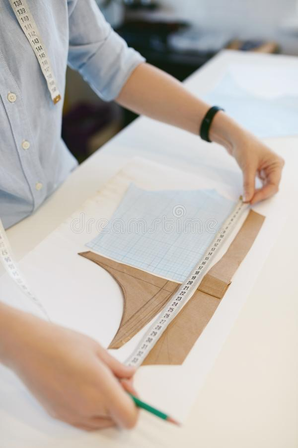 Female Tailor Measuring Sewing Pattern On Table stock image