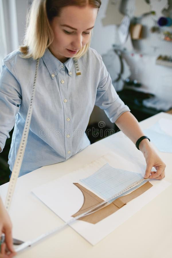 Female Tailor Measuring Sewing Pattern On Table stock photography