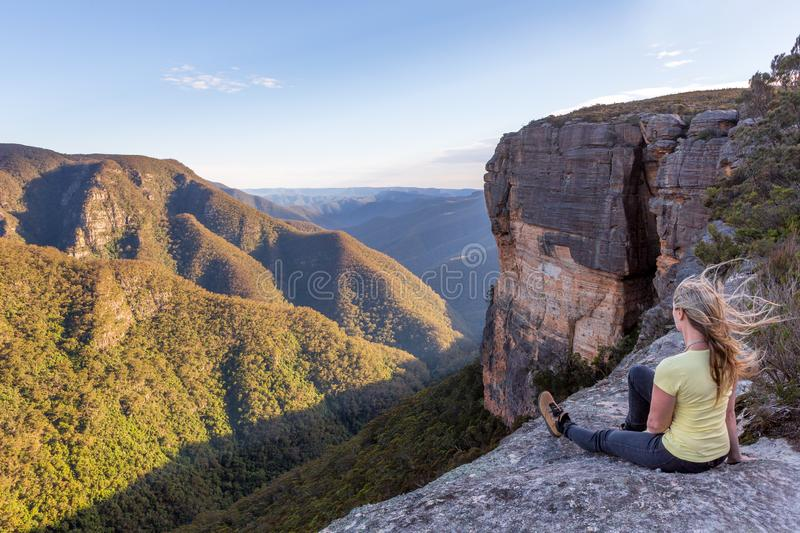 Woman takiong in beautiful mountain views from cliff top lookout. A female takes in magnificent views from the cliff top  of the mountainous landscape, with royalty free stock image