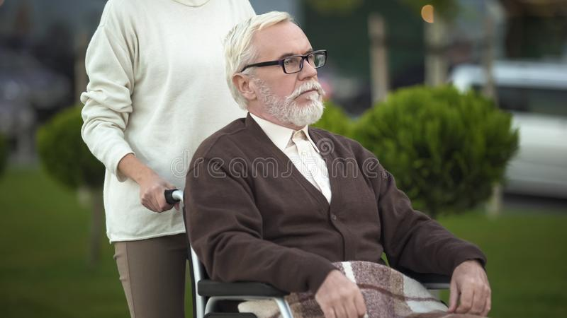 Female taking care of disabled grandfather wheelchair, family assistance, help stock images