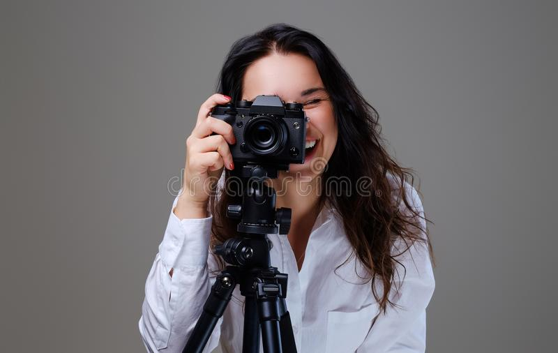 Female taking pictures with a professional photo camera. Smiling, positive brunette female in eyeglasses taking pictures with a professional photo camera stock photos