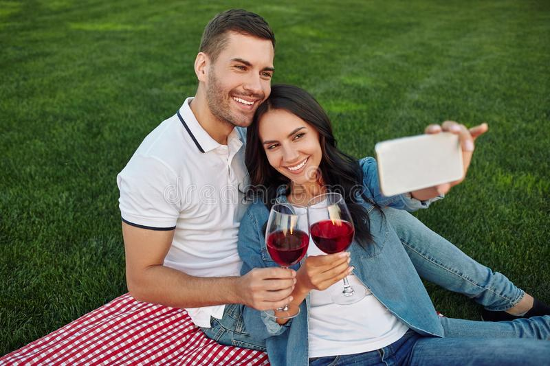 Female taking selfie on smartphone with her man stock photography