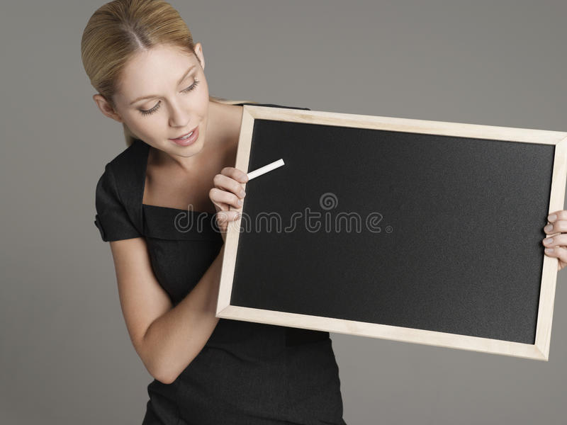 Female Teacher With Blackboard And Chalk. Young female teacher holding blackboard and chalk against gray background stock images