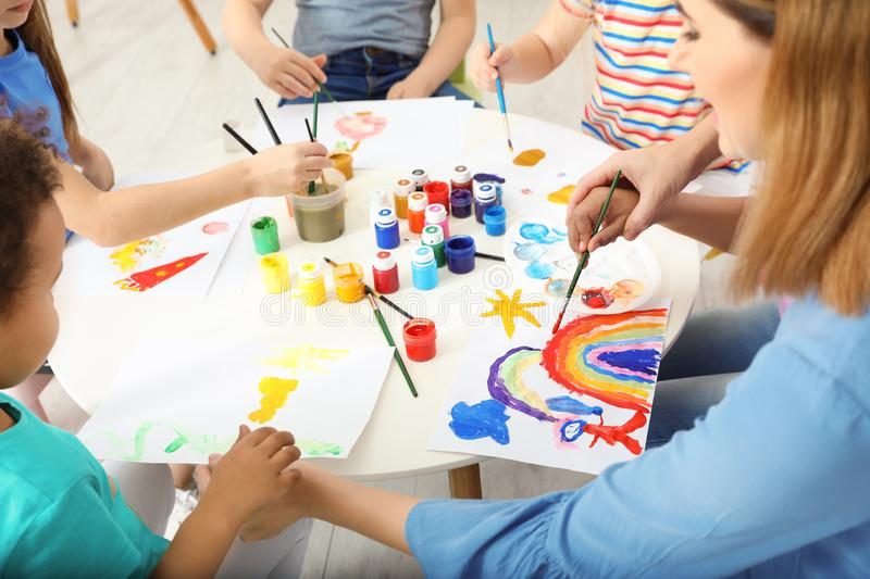 Female teacher with children at painting lesson stock photo