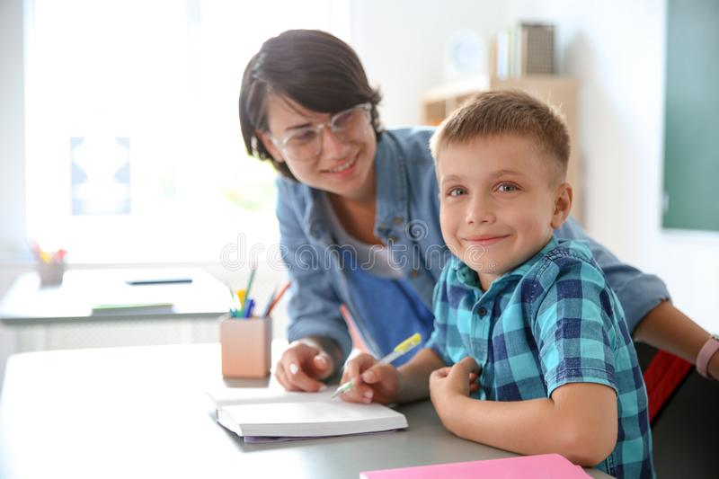 Female teacher helping child with assignment at school stock photography