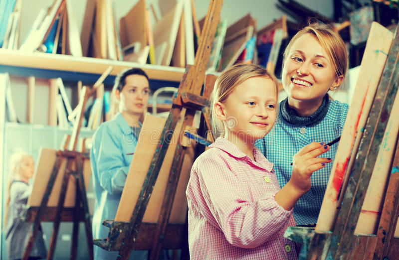 Female teacher helping girl during painting class royalty free stock photos