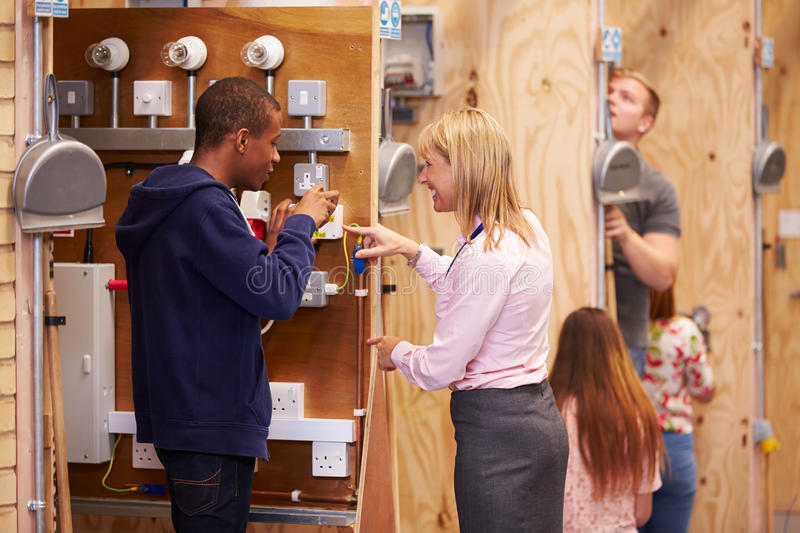 Female Teacher Helping Students Training To Be Electricians royalty free stock image