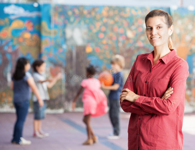 Female teacher with her elementary school kids playing outdoor royalty free stock image