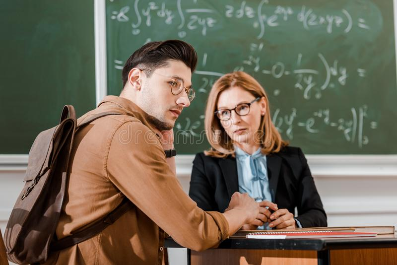 Female teacher looking at young student in classroom with chalkboard stock photography