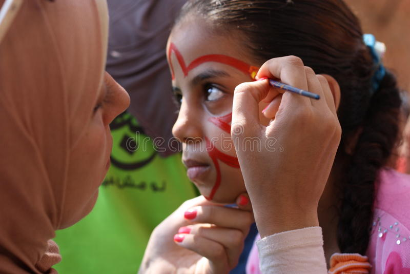 Female teacher painting little girls face in butterfly shape in playground stock photo