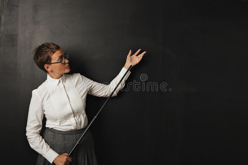 Female teacher with pointer at blackboard royalty free stock images