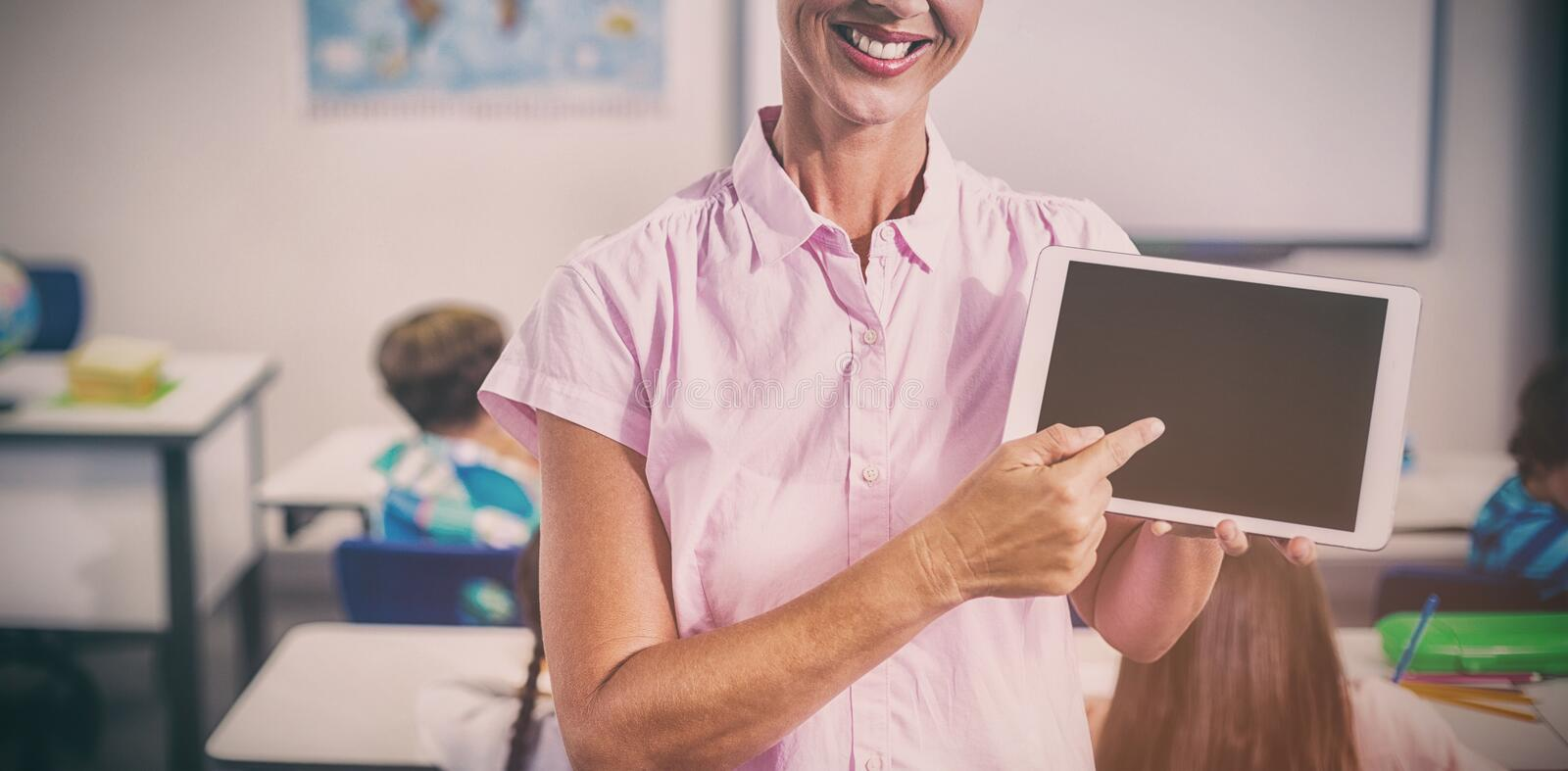 Female teacher pointing over digital tablet royalty free stock photography