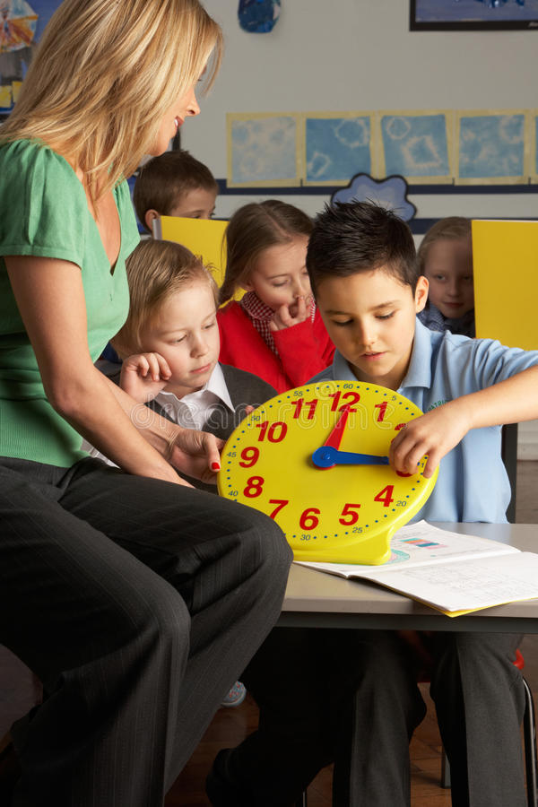 Download Female Teacher In Primary School Teaching Children Stock Photo - Image: 15540582