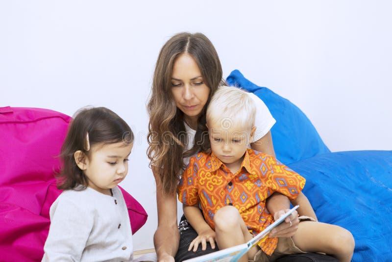 Female teacher reads a book to kids in kindergarten stock photo