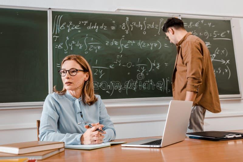 Female teacher sitting at desk near laptop while student stock image