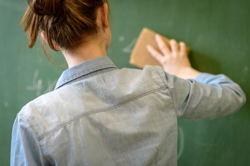 Female teacher or a student cleaning blackboard with a sponge. stock photo