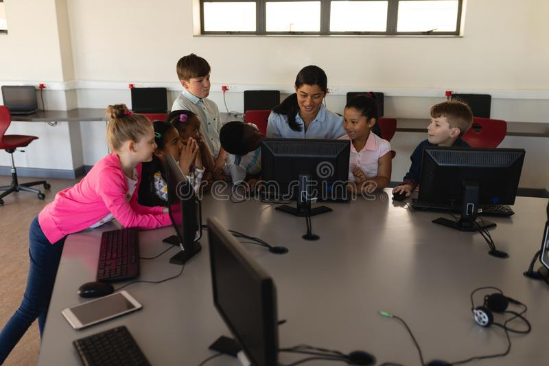Female teacher teaching computer to schoolkids at desk in school royalty free stock photos
